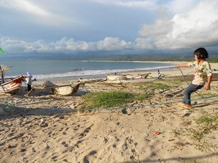 Seorang anak mencoba membantu orang tuanya menarik jaring, sambil bermain-main di Pantai Santolo.
