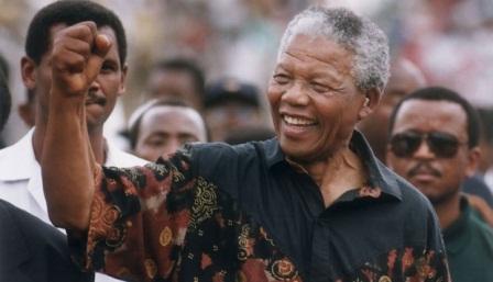 """Saat menghadapi hukuman mati, Nelson Mandela berbicara dari beranda atas Pengadilan Rivonia, April 1964: """"Selama hidup saya, saya mendedikasikan diri perjuangan bersama orang-orang Afrika. Saya berjuang melawan dominasi putih, juga berjuang melawan dominasi hitam. Saya menghargai kondisi ideal sebuah masyarakat demokratis dan bebas di mana semua orang hidup bersama dalam harmoni dengan kesempatan sama. Ini adalah hal saya harapkan terwujud dan untuk direalisasikan. Bila perlu, saya siap mati untuk itu."""" AP/The Star Tribune, Jerry Holt"""