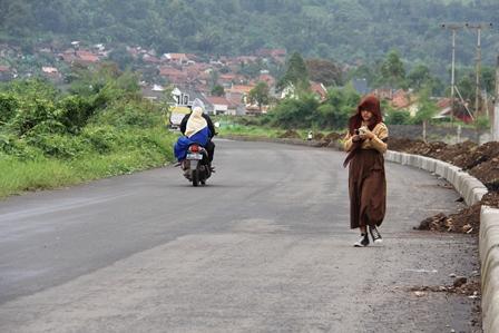Murid Prihatin Menyusuri Lintasan Jalan dengan sengatan matahari.