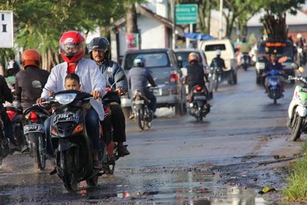 """Ilustrasi. Kondisi Jalan Wisata Menuju Situ Bagendit Hingga Kini Masih Dibiarkan """"Babak Belur"""". (Foto: John Doddy Hidayat)."""