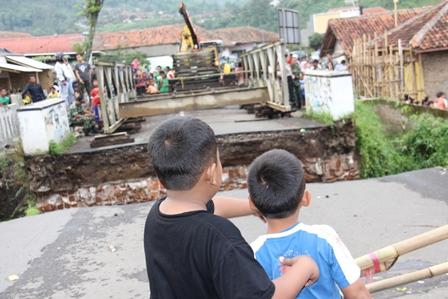 """Dua Bocah Saksikan Pemasangan Konstruksi """"Bailey"""". Selasa (04/03-2014). Foto: John Doddy Hidayat."""