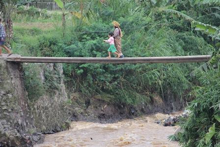 Seorang Ibu Tua Menuntun Cucunya Menapaki Jembatan Darurat Lintasi Sungai Cigunung Agung. (Foto: John Doddy Hidayat).