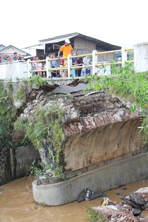 Pengawas Lapangan PU Bina Marga Provinsi Tertatih-Tatih Lintasi Sisa Kontruksi Jembatan Bangbayang. (Foto: John Doddy Hidayat).