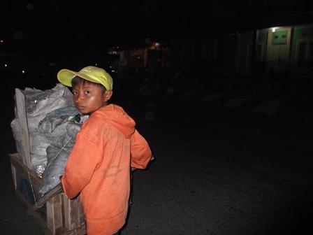 Anak Kelas Empat SD Ini Membantu Orang Tua Mendorong Roda Sampah.