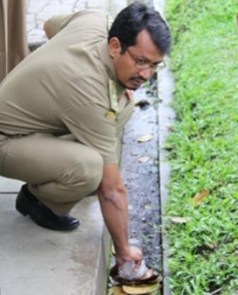 Wabup Helmi Budiman, Memberi Contoh Pungut Sampah di Pelataran Dinas SDAP Garut. (Foto: John Doddy Hidayat).
