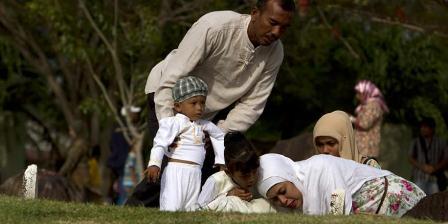 Warga melihat tulisan pada batu nisan seusai berdoa dan menabur bunga di kuburan massal korban gempa dan tsunami, Ulee Lheue, Kecamatan Meuraxa, Banda Aceh, dalam peringatan sembilan tahun tsunami Aceh, Kamis (26/12/2013). Gempa dan tsunami pada 26 Desember 2004 silam menyebabkan sekitar 230.000 korban meninggal serta ratusan ribu bangunan rusak. (SERAMBI/BEDU SAINI).