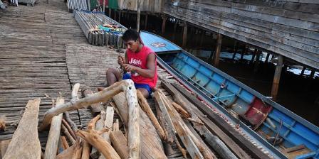 Salah seorang warga bajo di Desa Hakatutobu yang sedang membelah kayu bakar. (KOMPAS.com/ Suparman Sultan).