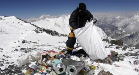 Seorang sherpa atau pemandu gunung membersihkan tumpukan sampah di gunung paling tinggi di dunia Everest. Banyak pendaki tertantang untuk menaklukan gunung ini, namun para pendaki juga meninggalkan banyak sampah. Nepal, 23 Mei 2010. Namgyal Sherpa/Getty Images.
