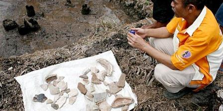 Warga berupaya mengeringkan air yang menggenangi situs Air Sugihan di Desa Kerta Mukti, Kecamatan Air Sugihan, Kabupaten Ogan Komering Ilir, Sumatera Selatan, Jumat (9/10). Situs Air Sugihan berupa tiang rumah panggung dari kayu nibung, yang berasal dari masa sebelum Sriwijaya, yaitu sebelum abad VII Masehi. Di tempat itu juga ditemukan pecahan keramik, manik-manik, dan lain-lain. KOMPAS/WISNU AJI DEWABRATA