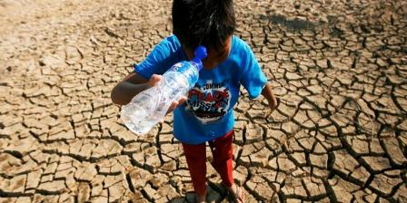 Mamat (10) mencuci muka untuk mengusir panas dari botol bekal air minumnya saat bermain di sekitar kolam salah satu sumber air untuk warga Kampung Campaka, Desa Cihampelas, Kabupaten Bandung Barat, Jawa Barat, yang mengering, Rabu (29/7). Sejak sebulan terakhir, debit air kolam tersebut terus menyusut hingga pada akhirnya kering saat musim kemarau ini. Mengeringnya kolam dan menyusutnya debit air sejumlah sumber air bersih dirasakan menyulitkan warga. (KOMPAS/RONY ARIYANTO NUGROHO).