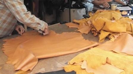 Proses pemotongan dan menjahit jaket kulit.