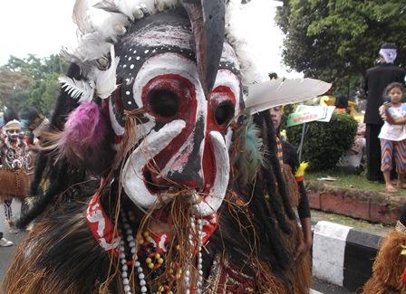 Seorang Anak Memotret Tampilan Seni Tari Papua.