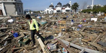 Seorang lelaki melintasi reruntuhan yang terempas tsunami dari Samudera Hindia hingga ke depan Masjid Raya di Banda Aceh, Nanggroe Aceh Darussalam. Gambar diambil pada 29 Desember 2004. (AP/Dita Alangkara)