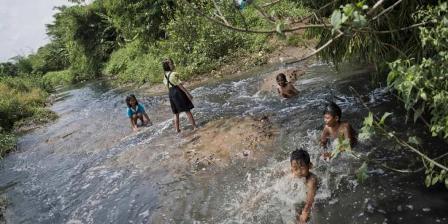 Anak-anak mandi di Sungai Cikijing yang tercemar dengan limbah industri tekstil di Rancaekek, Bandung, yang airnya mengalir ke Sungai Citarum, 22 Maret 2015. (AFP PHOTO / ROMEO GACAD).