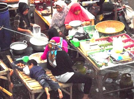 Seorang Bocah Tertidur Pulas, Sedangkan Ibu Kandungnya Sibuk Melayani Para Pembeli.