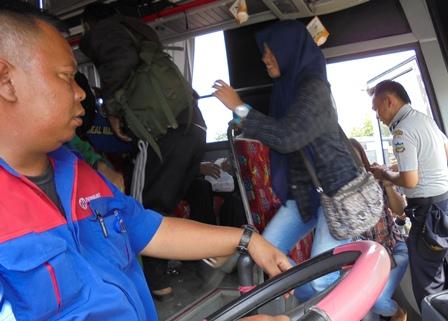 Petugas Dishub Membantu Penumpang Memasuki Bus.
