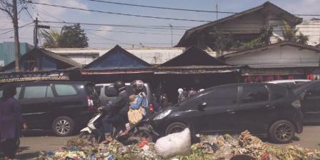 Pengendara sepeda motor saat melintasi tumpukan sampah di Pasar Andir Kota Bandung, Jalan Rajawali, Selasa (9/8/2016). Sampah hasil berjualan pedagang yang ditumpuk di badan jalan menjadi secuil masalah buruknya tata kelola pasar di Kota Bandung. (KOMPAS.com/Dendi Ramdhani).