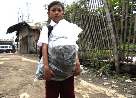 Seorang Siswa Membawa Seperangkat Peralatan Sekolah Termasuk Seragam, Sumbangan Presiden.