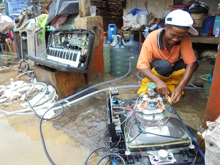 Seorang Montir Elektronik Membersihkan dan Kembali Memerbaikinya.