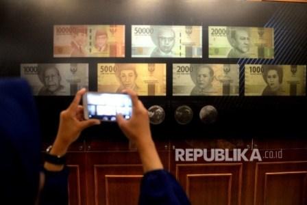 Pengunjung memotret uang Rupiah baru usai peresmian pengeluaran dan pengedaran uang Rupiah Tahu Emisi 2016 di Bank Indonesia, Jakarta, Senin (19/12). Republika/ Wihdan.