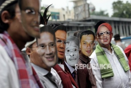 Warga yang tergabung dalam kelompok Bangga Jakarta melakukan aksi damai menggunakan topeng pasangan calon Gubernur DKI Jakarta saat menyampaikan Petisi Pilkada Damai di depan Kantor KPU DKI Jakarta,Jakarta Pusat, Kamis (13/10).  Republika/Rakhmawaty La'lang.
