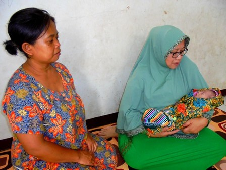 Sasa Mutiara Al Huntara Dipangku Seorang Dermawan, Disaksikan Nenek Bayi tersebut, Ny. Lina, Rabu (19/04-2017). Ny. Lina, nenek bayi pengungsi banjir bandang sama sekali tak mengijinkan cucunya dipelihara oleh negara melalui Kementerian Sosial maupun Dinas Sosial manapun, meski Rosa (19) ibu kandung bayi tersebut meninggal dunia setelah empat hari melahirkan anak pertamanya perempuan, yang diberinya nama Sasa Mutiara Al Huntara.