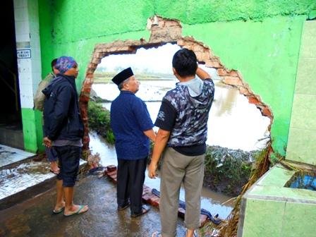 KH. Aceng Zakaria Mengamati Tembok Pagar Permanen yang Jebol Dihantam Banjir.