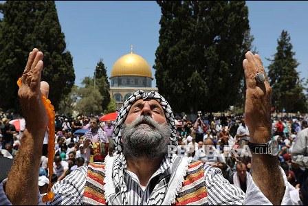 Seorang warga Palestina berdoa di kompleks Masjid Al-Aqsha dengan latar belakang Masjid Qubbah AS-Shakhrah (Masjid Dome of Rock).. (Ammar Awad/Reuters).